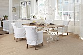 White loose-covered armchairs around dining table in bright interior