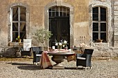 Round stone table and black outdoor armchairs outside vintage country house