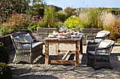 Set wooden table and rattan furniture on terrace in summery garden