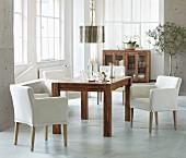 weiße Armlehnsessel und massiver Edelholztisch in hellem Ambiente mit Industrieverglasung