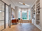 Fitted shelving, herringbone parquet and seating area in window bay in classic interior