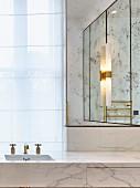 Moderner Glamour im Badezimmer mit Marmor, Gold und Spiegel