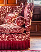 Classic sofa with red and white ornamental pattern and fringed trim