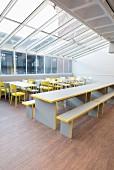 Tische, Stühle und Bänke in Grau und Gelb unter einem Glasdach