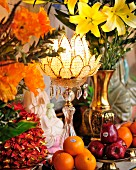 Flower-shaped candle lantern amongst opulent arrangement of flowers and fruit