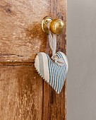 Blue and white striped fabric love-heart hung from knob of wooden door