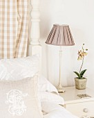 Bedside lamp with ruched lampshade next to orchid