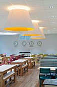 Large ceiling lamps and various tables and chairs in canteen