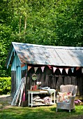Wooden hut with corrugated metal roof decorated with colourful fabric bunting in garden