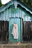 Floral fabric and felt flower hung from clothes hanger on board door of traditional wooden hood