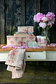 Romantic vintage-style still-life arrangement of peonies and decorative cardboard boxes against rustic board wall