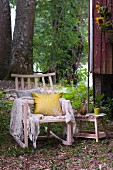 Cushions and blanket on comfortable wooden rocking chair outside wooden hut