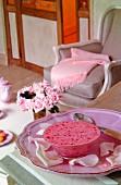 Pinkes Dessert auf rosafarbenem Teller mit Rosenblättern