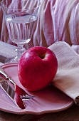 Pink apple and cutlery on pink plate next to glass of water