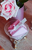 Soap wrapped in pink paper with label next to rose
