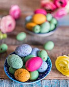 Colourful speckled eggs in bowls