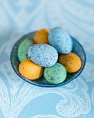 Colourful speckled eggs in bowl on pale blue tablecloth