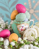 Colourful speckled eggs in vintage gold-rimmed teacup arranged with white flowers