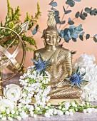 Buddha figurine decorated with white flowers and Eryngium flowers