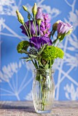 Arrangement of purple flowers in glass vase in front of wall with floral pattern
