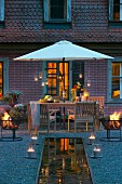 Fire bowls and candle lanterns arranged around pool in front of terrace in summer twilight