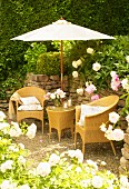 Romantic seating area with wicker furniture below parasol against stone wall