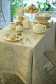 Staked china, tea service and pastries on elegant tablecloth on balcony table