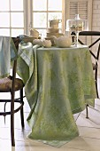 Stacked china, teapot and glass cake stand on round table with pastel-green tablecloth