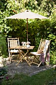 Bamboo furniture below parasol in secluded seating area in garden