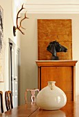 Ceramic pot on exotic-wood table in front of bust of horse and hunting trophy