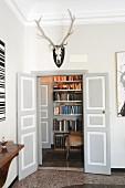 Flügeltür unter Jagdtrophäe und Blick auf Bücherregal