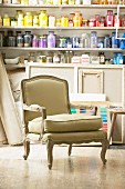 French-style armchair in front of jars of pigments on shelves