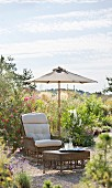 Wicker armchair and stool under parasol in summer garden