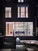 Blick von der Terrasse ins beleuchtete Haus mit Essbereich im Erdgeschoss