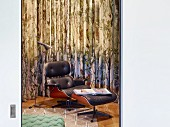 Classic Eames Lounge Chair with black leather upholstery and matching footstool in front of curtain