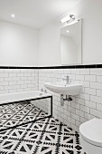 Black and white floor tiles and bathtub with mirrored side in bathroom