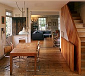 Table and cantilever chairs on wooden floor in dining room with staircase to one side