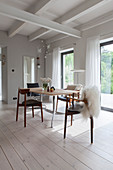 Sheepskins on designer chairs in dining room with white floor