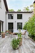 Gemütlicher Sitzplatz auf der Terrasse vor modernem Haus