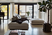 Sofa and ottoman in loft apartment with concrete floor and glass wall