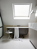 Free-standing bathtub under sloping skylight and against crooked knee wall