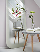 Concrete side table in front of full-length mirror with frosted rim