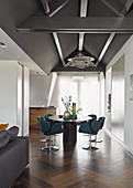Blue upholstered chairs around oval dining table below exposed roof structure