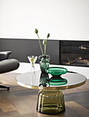 Poppy seedheads in vase on round coffee table with glass base