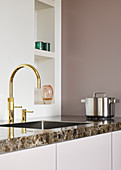 Gold sink tap fitting in minimalist kitchen