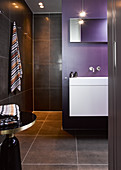 Modern bathroom with black tiled and purple wall