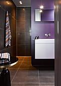 Modernes Bad mit schwarzen Fliesen und violetter Wand