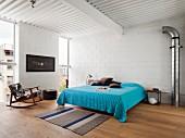 Doppelbett mit blauer Tagesdecke und Schaukelstuhl im Schlafzimmer mit weiss gestrichenen Betonblöcken
