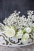 White ranunculus and gypsophila in white metal basket