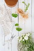 Blumen und Floristikutensilien auf weißen Brettern